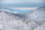A clearing October storm leaves Cherokee National Forest (foreground) and the Great Smoky Mountains (far background) blanketed in snow, TN