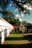 Visitor shaded by red umbrella walks in Lafayette Cemetery