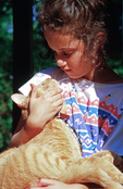 Eight year old girl lovingly holding her cat