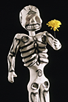 MEXICO. Mexico City. papier maché skeleton with flower of the Dead called cempasuchil or French Marigold on sale in a shop for the day of the Dead in November.