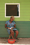 HONDURAS. In Trujillo on the coast, black lady reading in front of her wooden painted house.