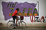 "CUBA. Santiago de Cuba, black lady on bike in front of a mural representing sugar cane. The letters of the word ""Zafra"" meaning sugar cane harvest have the shape of the the plant leaves."