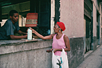 CUBA. Havana. Woman buying milk with a rationing ticket.