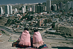 BOLIVIA, Andes, La Paz. Two Aymara Indian women wearing the traditional costume looking at La Paz.
