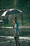 INDONESIA Java Javanese woman wearing the traditional sarong walking in the rain.