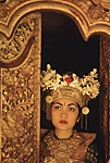 INDONESIA, Bali : Legong dancer posing in traditional costume at the gilded carved wood door of a palace.