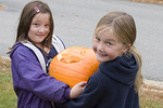 Two Girls Carrying Their Carved Pumpkin to the Pumpkin Contest