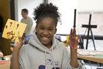 Girl Makes a Hand Print in an Art Class