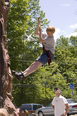 Boy Uses a Rope to Repel Down a Climbing Wall