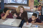 Teacher Helps Two Students With Their Reading Assignment
