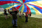 First Graders Play Under a Colorful Parachute