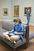 A young woman uses her IPAD to take notes in a museum