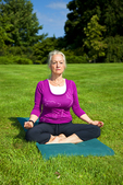 Woman meditating and doing yoga outside on grass