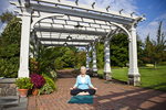Yoga instructor sitting under a trellis and meditating