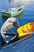 Three rowboats tied up to a dock in Rockport, Massachusetts Harbor