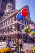 Balloons decorate the marketplace at Quincy Market with Faneuil Hall in the background.