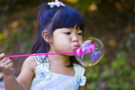 Young girl blows a big bubble