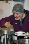 Man dishes up some soup from a kettle