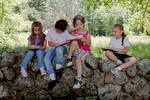 Four girls sitting on a stonewall doing their school work at an outdoor class