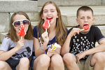Three children enjoying an ice cream bar on a hot day.