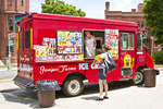 An ice cream truck dishes out ice cream on hot summer day