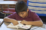 Young hispanic boy reading in the classroom