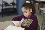 Young hispanic girl reading a book in the classroom