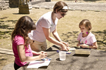 Young woman helping two young girls with their watercolors
