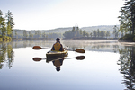 Woman kayaking in the early morning on a New England Lake