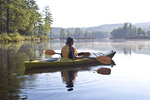A woman kayaking on a very calm lake in Royalston, MA