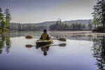A woman looks out on the calm waters of Tully lake from her kayak