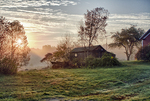 Sunrise over a rural farm - the morning sunlight filtered by early morning mist.