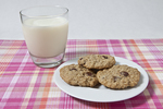 Three cookies on a plate with milk
