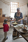 Costumed interpreter cooks at Coggeshall Farm while a visitor looks on