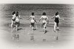 Five girls running into the Atlantic Ocean at Crane Beach