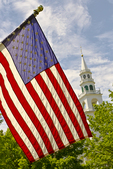 American flag on the common in Templeton, MA with the Congregational church steeple in the background