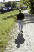 Woman walking a country road in Vermont