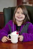 Little girl enjoys a cup of hot chocolate