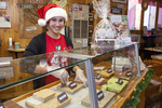 Teenage girl dressed up for Christmas serves fudge at a store
