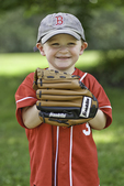 The baseball glove is bigger than the 3 year old boy