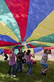 Children playing under a parachute #4