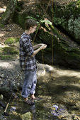Young man attaching a fly to his fly rod