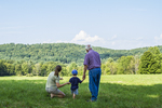Little boy with mother and grandfather looking out over a meadow