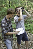 Two birdwatchers, one consulting a bird guide book