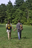 Couple walking hand in hand in a meadow