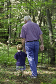 Man and his grandson walking in the woods