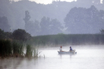 Two people fishing in a boat on a foggy morning