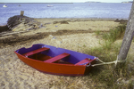 Red rowboat tied up on the beach