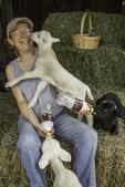 Farmer bottle feeding newborn lambs