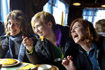 Three women eating pancakes and having a very good time.